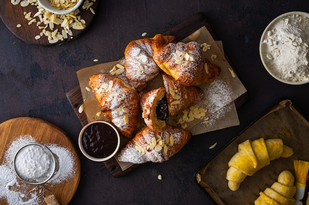 Fresh croissants with chocolate on a dark stone