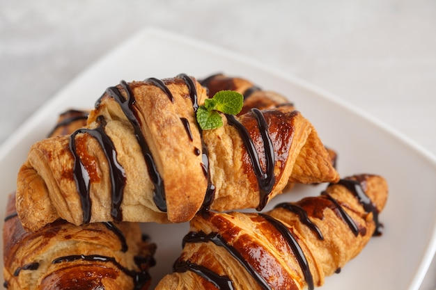 Fresh croissants with chocolate syrup on a light gray background, copy space. french cuisine dessert concept.