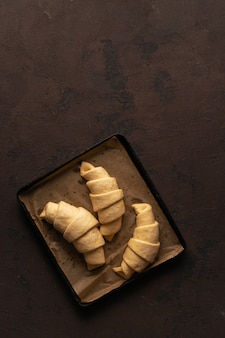 Fresh croissants with chocolate on a tray top view