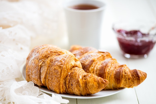 Fresh croissants with icing, cup of tea and strawberry jam