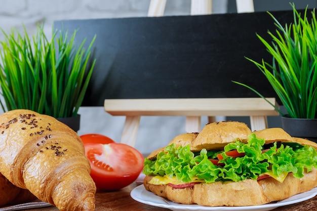 木製のテーブルの上の白いプレートに豚肉、鶏肉、トマト、きゅうり、サラダと焼きたてのクロワッサン。あなたのテキストのための黒板。