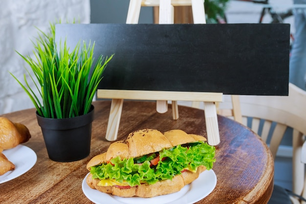 木製のテーブルの上の白いプレートにポークチキントマトきゅうりのサラダと焼きたてのクロワッサン。黒のコピースペース。