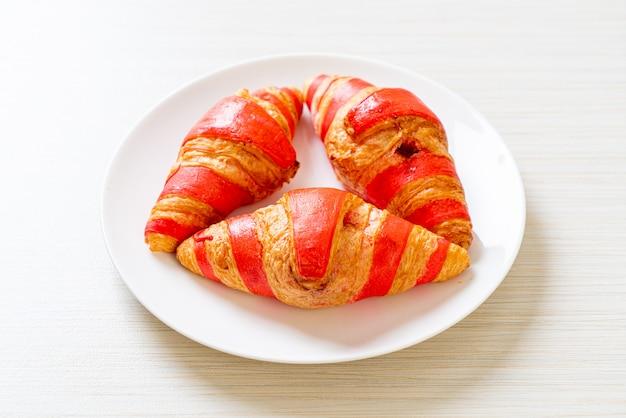 Свежие круассаны с клубничным джемовым соусом на тарелке