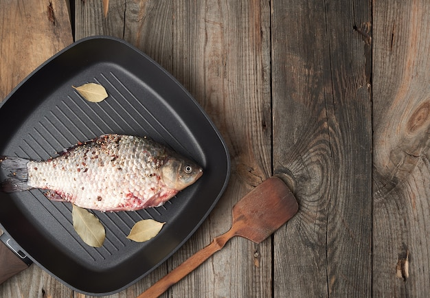 Fresh crucian fish sprinkled with spices and lies in a black square pan