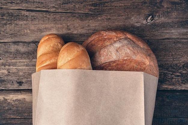 Fresh, crusty bread in a bag on a wooden surface