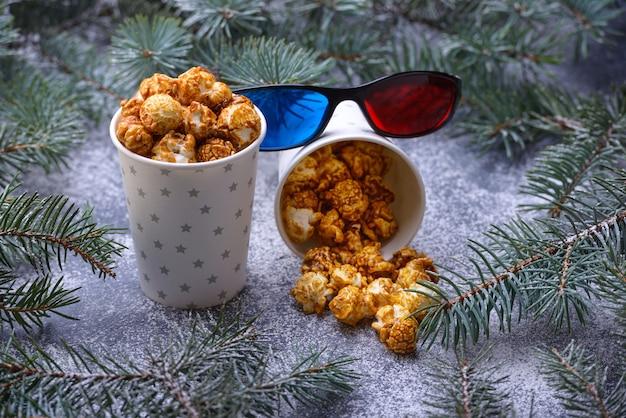 クリスマスツリーと装飾の横にある紙コップの新鮮な無愛想な自家製ポップコーン