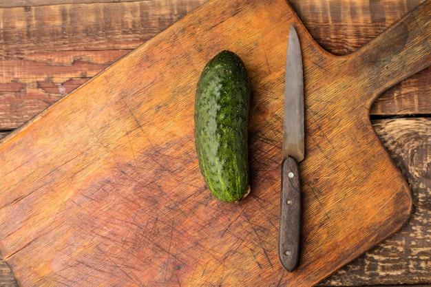 木製のまな板に新鮮なキュウリとナイフ。上を表示します。コピースペース