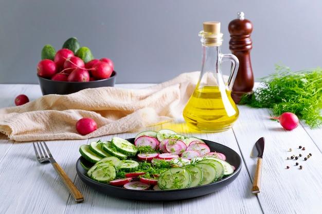 新鮮なキュウリと大根のサラダ、ディルと植物油。ベジタリアンダイエット。減量のためのディエスタ。健康的な食事。セレクティブフォーカス。