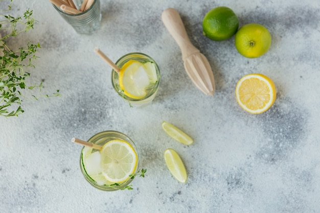 グラスに入った新鮮なキュウリのカクテル。木製のテーブルにキュウリ、ライム、タイム、角氷と夏のカクテル