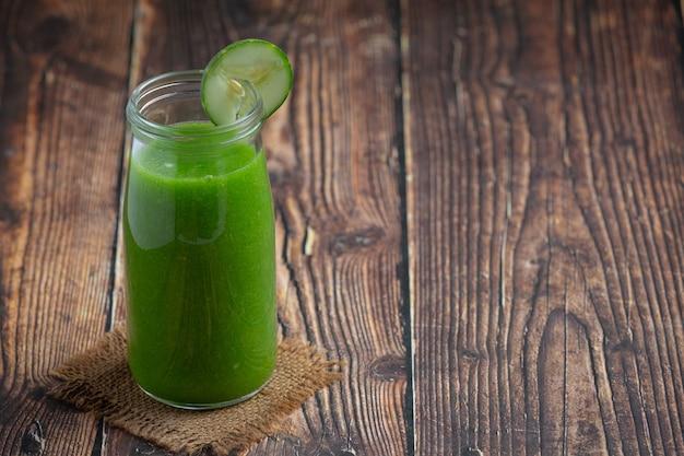 Fresh cucumber juice in a jar on dark wood background