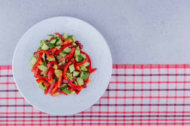 Салат из свежих огурцов, перца и салата на скатерти на мраморном фоне. фото высокого качества