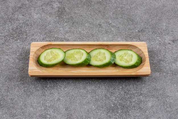Fette di cetriolo fresco su tavola di legno su superficie grigia
