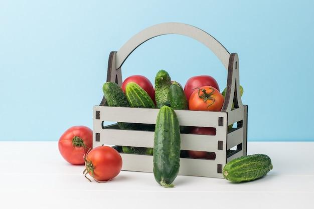 파란색 배경에 흰색 테이블에 나무 상자에 신선한 오이와 토마토. 야채의 신선한 작물입니다. 프리미엄 사진