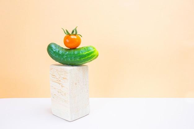新鮮なキュウリとトマトは、明るいニュートラルスペースの木製の表彰台に。野菜の収穫のコンセプト、健康的な有機食品。ミニマリズム、コピースペース。