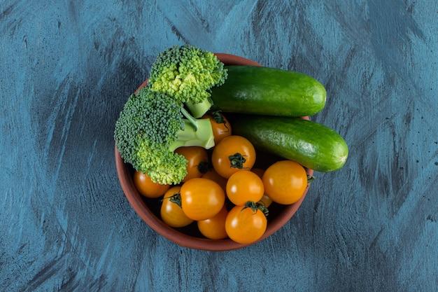 Свежие огурцы, помидоры черри и брокколи в керамической миске.