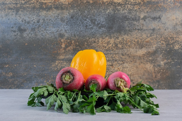 Свежие огурцы, красный редис и перец на каменном столе. фото высокого качества