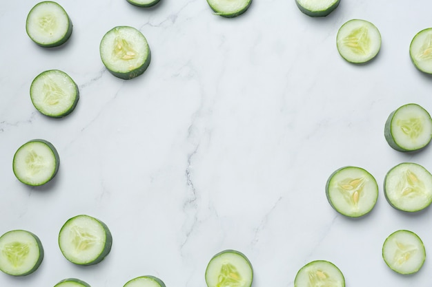 Fresh cucumbers sliced on marble background