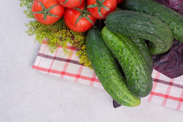 Свежие огурцы, помидоры и базилик на скатерти