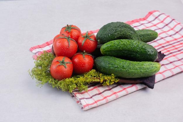 Свежие огурцы, помидоры и зелень на скатерти