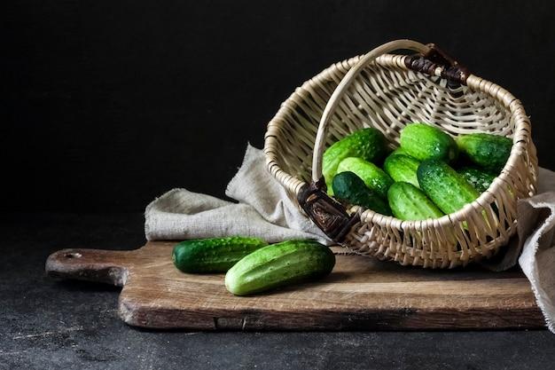 Fresh cucumbers in wicker basket on wooden board on black background.