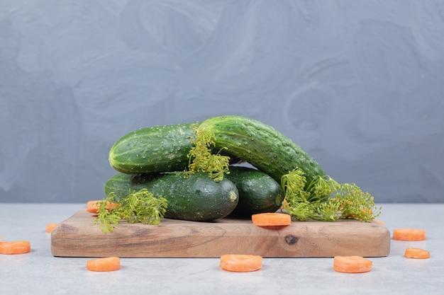 Cetrioli freschi con fette di carota su tavola di legno. foto di alta qualità