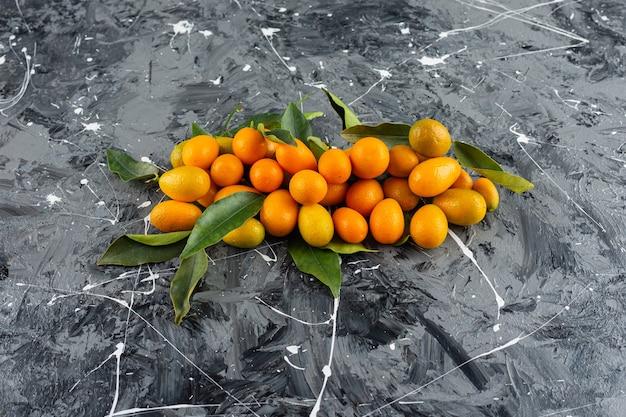 잎을 가진 신선한 cumquat 과일은 대리석 테이블에 놓입니다.