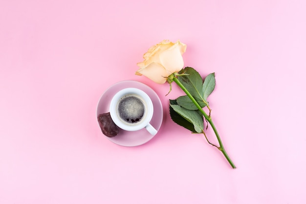 Fresh cup of coffee and a beige fragrant roses on a pastel pink background, flat lay