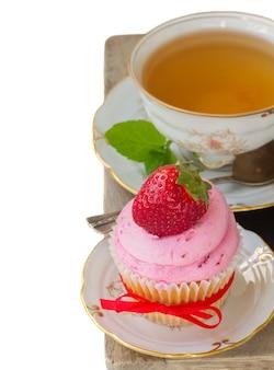 Свежий кекс с красной клубникой в бордюре тарелки, изолированные на белом фоне