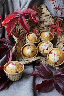 さくらんぼを詰めた新鮮なカップケーキを籐のかごに入れ、紅葉で飾ります