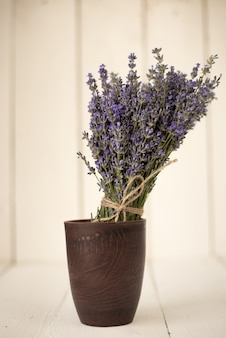 Fresh cut aromatic bouquet of lavender field in a wooden glass on white wood.
