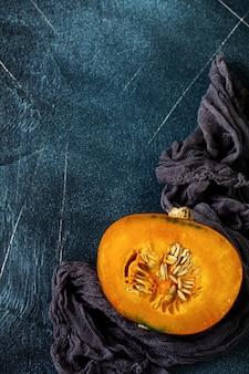 Fresh cut in half pumpkin with gray napkin on old stone dark blue