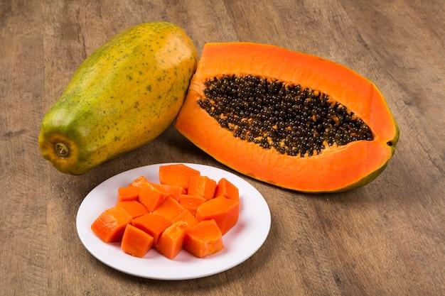 Свежесрезанные сочные тропические фрукты мамао папайи с семенами по-бразильски. свежие фрукты