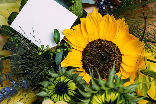 Fresh cut sunflowers in bouquet and card with envelope with copy space