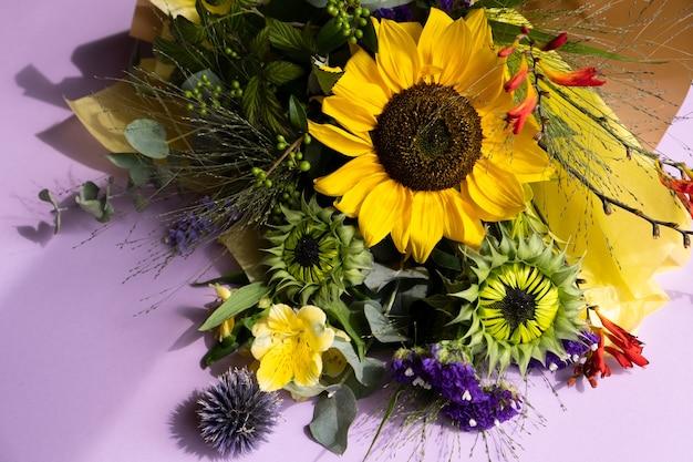 Fresh cut sunflowers in bouquet on purple background