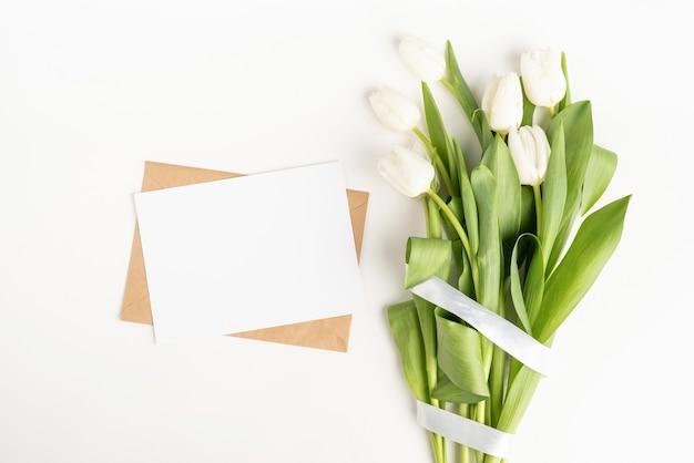 신선한 잘라 흰색 튤립 꽃과 흰색 배경에 봉투 평면도와 빈 카드
