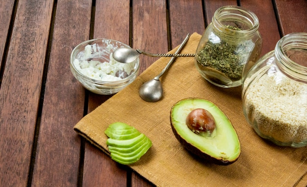 Fresh cutted avocado with sesame, soft cheese and herbs. copy space