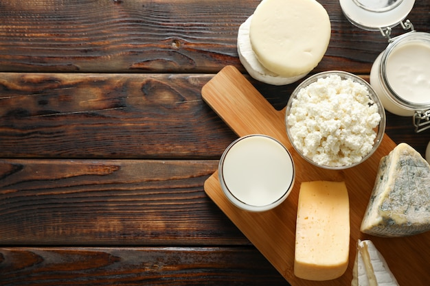 Fresh dairy products and cutting board on wooden background