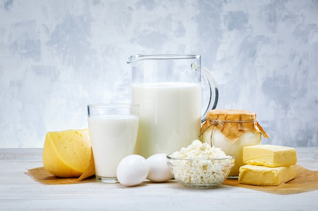 Fresh dairy products, milk, cheese, eggs, yogurt, sour cream and butter on white wooden table