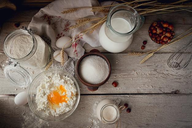 Свежие молочные продукты. молоко, творог, сметана и пшеница на деревенском деревянном фоне. молочная концепция органического земледелия. вид сверху