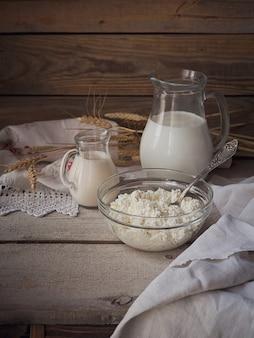 신선한 유제품:우유, 코티지 치즈, 사워 크림, 밀이 소박한 나무 배경에 있습니다. 유기농 낙농 개념입니다.