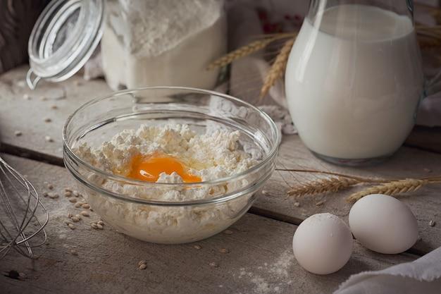 신선한 유제품:우유, 코티지 치즈, 사워 크림, 신선한 계란, 밀이 소박한 나무 배경에 있습니다. 유기농 낙농 개념입니다.