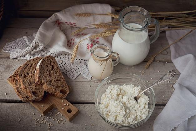 신선한 유제품. 소박한 나무 배경에 우유, 코티지 치즈, 사워 크림, 멀티그레인 홈메이드 빵, 밀. 유기농 낙농 개념입니다.