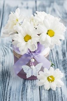 Fresh daisy flowers in purple glass