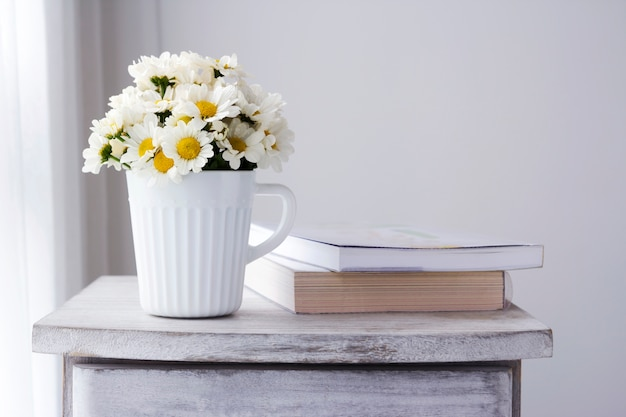 Fresh daisy flowers in white cup on wooden cabinet