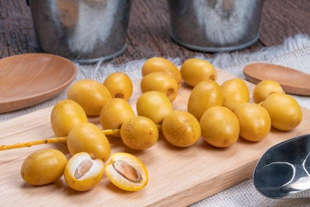 Свежие плоды финиковой пальмы на деревянной тарелке, сладкие желтые плоды финиковой пальмы.