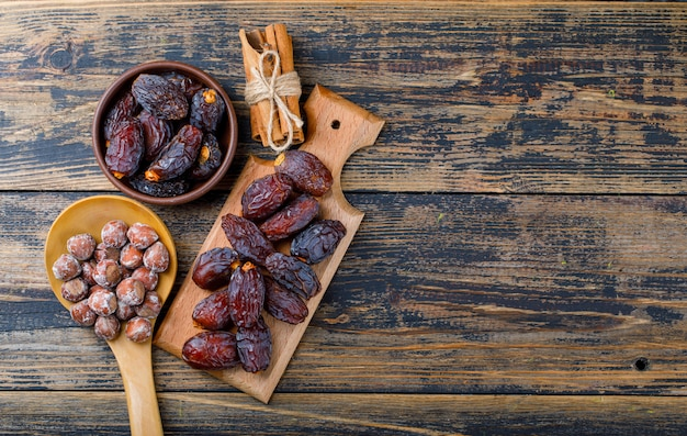 Fresh dates in bowl and cutting board with nuts in wooden spoon and cinnamon sticks top view on wooden background