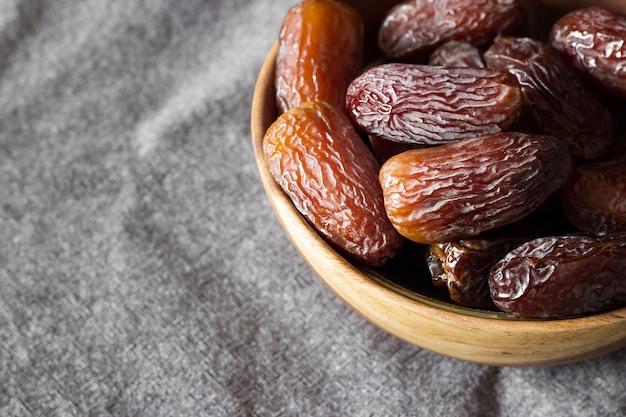 Fresh dates medjool in wooden bowl in upper right corner, on dark grey background. selective focus.