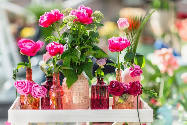 Fresh and decorative artificial roses in different vases