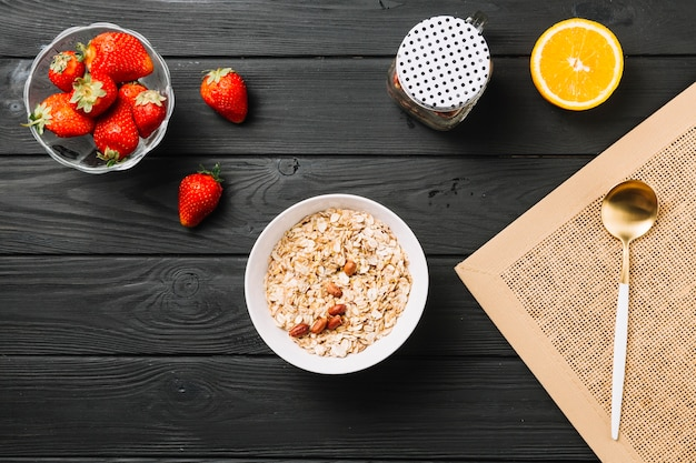 Fresh delicious breakfast with fruits on textured wooden plank
