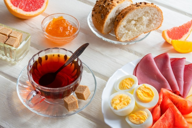 부드러운 삶은 계란, 치즈, 햄 신선한 빵과 컵 커피 또는 차 밝은 나무 배경에 신선한 맛있는 아침 식사.
